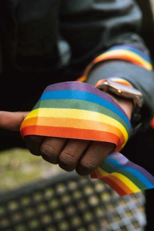 Crop unrecognizable black gay wearing rainbow ribbon on arm