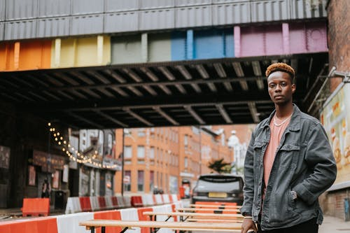Black man standing near city bridge painted in rainbow colors