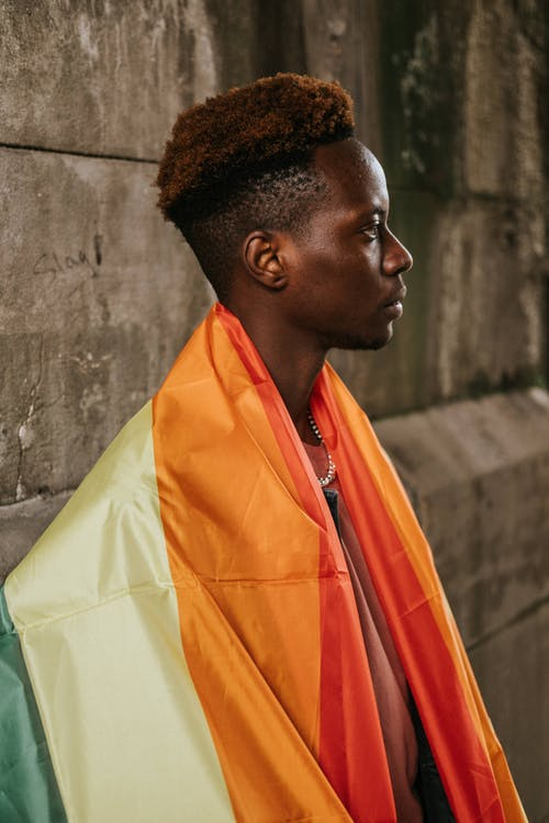 Contemplative young African American homosexual male with dyed hair standing on street with colorful LGBT flag on shoulders and looking away