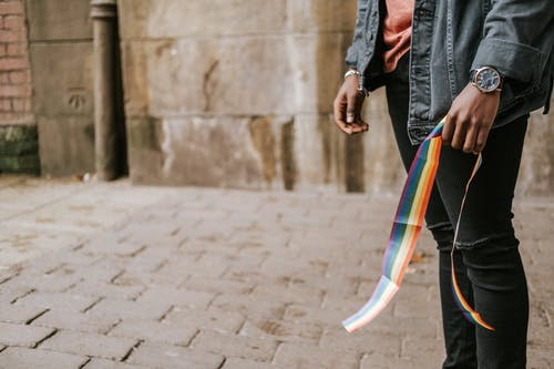 Crop anonymous African American male in casual clothes standing on street sidewalk with colorful rainbow ribbon in hand
