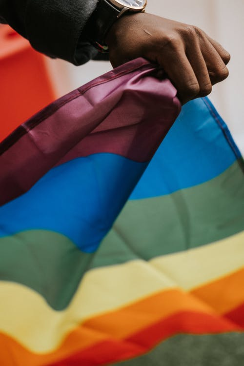 Unrecognizable African American guy with pride flag during parade