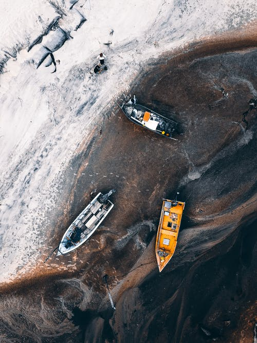Top view of vessels moored near sandy shore on abandoned terrain of island