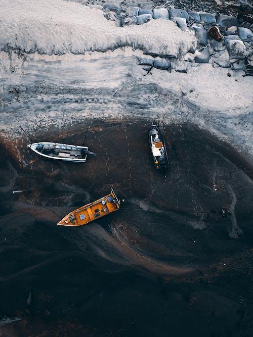 Boat sailing near rocky rough sandy coast