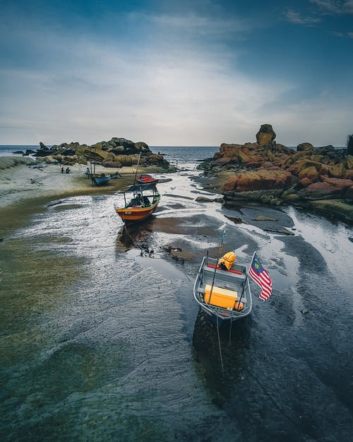 Small boats with flag moored in water on stony coast