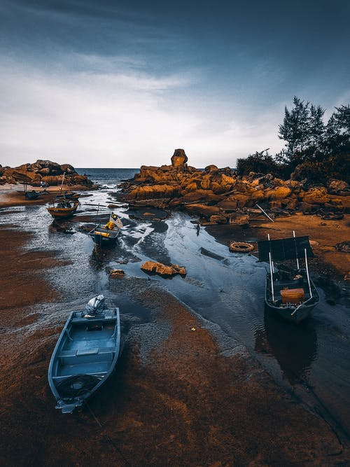 Vessels placed on sandy rocky wet shore of ocean under cloudy bright blue sky