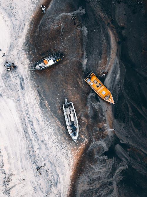 Boats moored near sandy shore of ocean