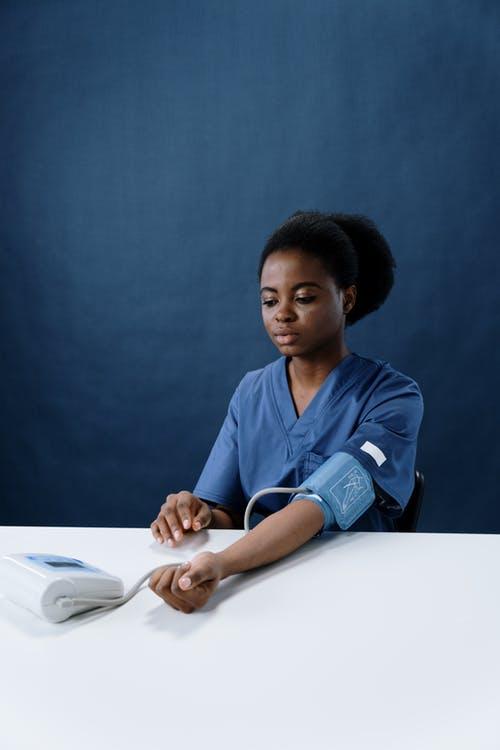 A Healthcare Worker Measuring Her Own Blood Pressure Using a Sphygmomanometer