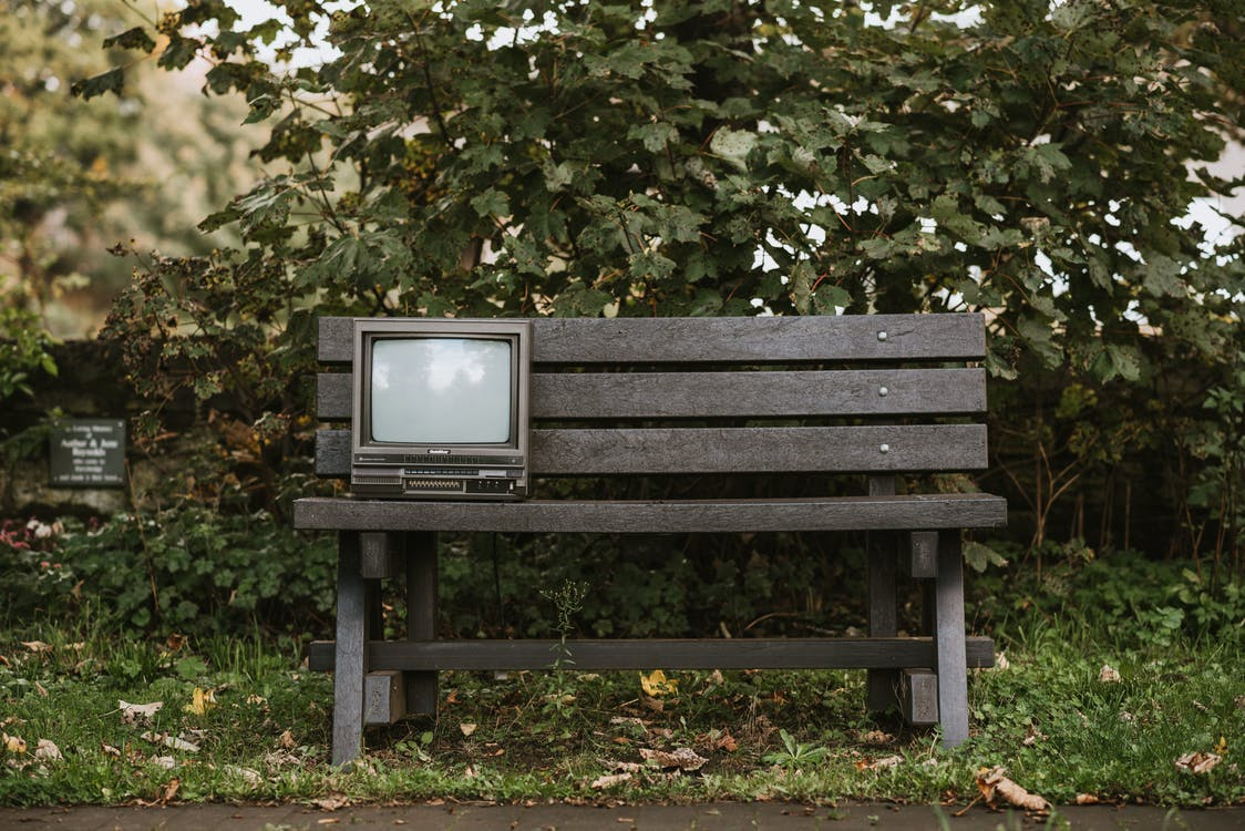 Old TV set on bench in nature