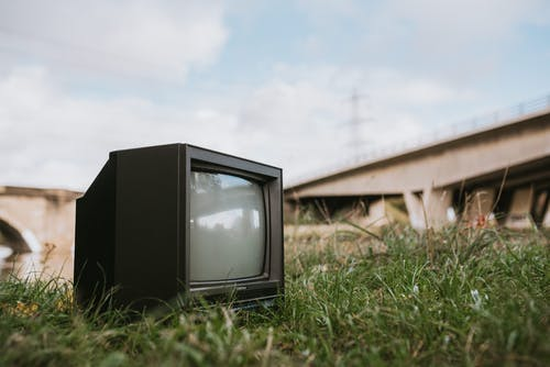 Vintage TV set on grassy seashore