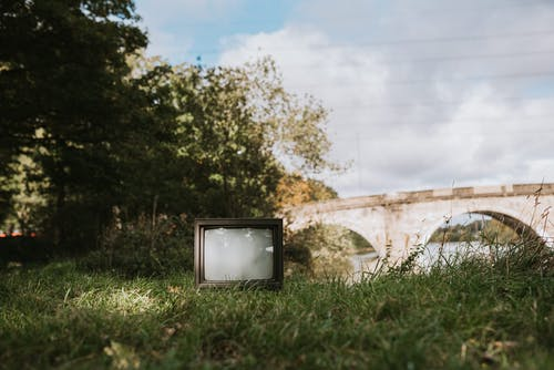 Old TV set on grassy coast