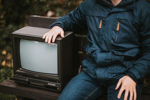 Crop man sitting on bench with retro TV set