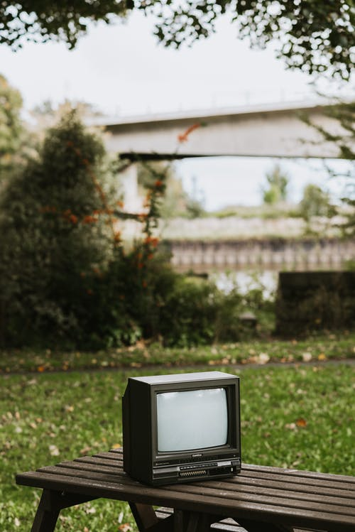 Small black old fashioned television placed on bench in city on street with green plant and bridge on blurred background