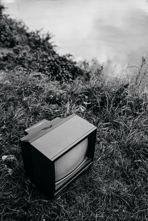 Black and white from above of old fashioned television placed on grassy coast near calm lake on embankment in nature