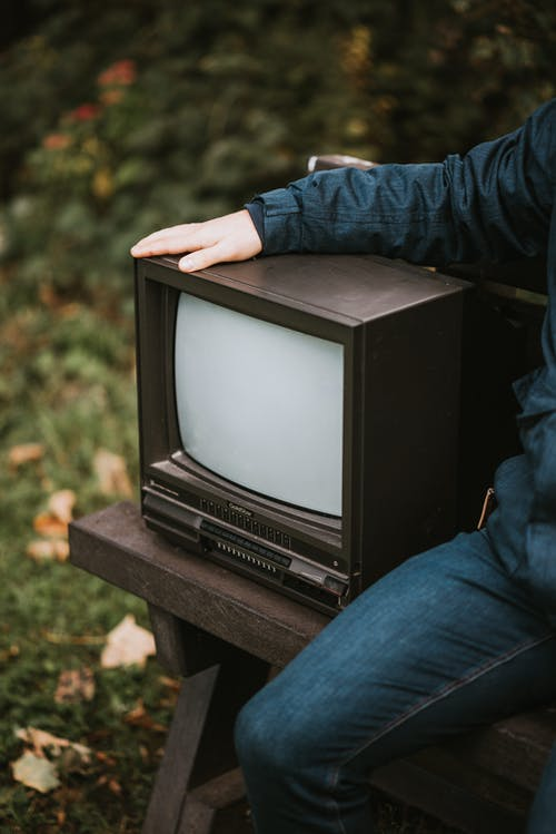 Crop man with old TV set in park