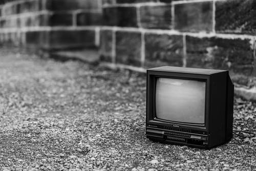 Black and white of old fashioned television placed on pathway near stone fence in city on street on blurred background