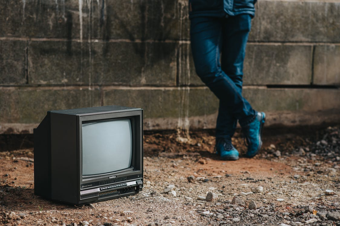 Crop person standing near fence and old TV