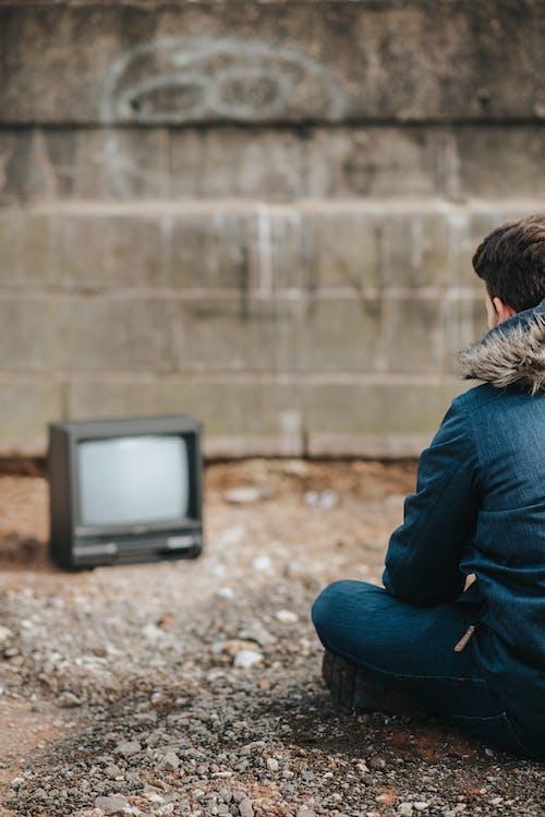 블루 데님 재킷과 블루 데님 청바지 블랙 Crt Tv와 함께 바닥에 앉아있는 여자