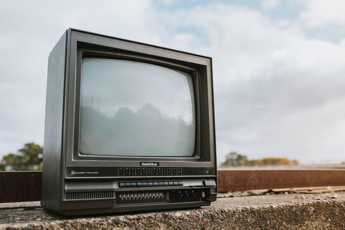 Vintage TV set placed on stone barrier