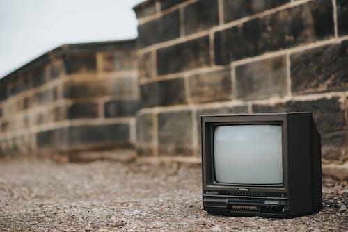 Small retro TV on ground near stone barrier