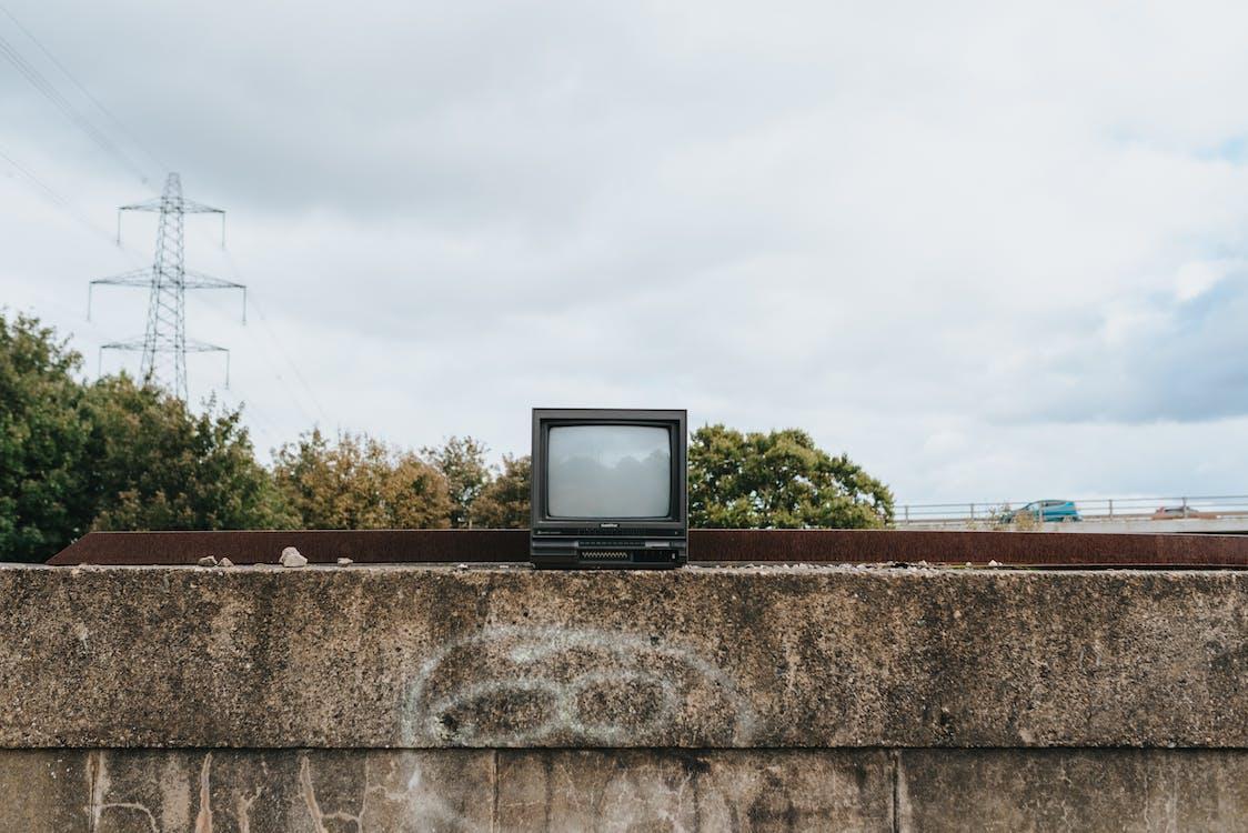 Small vintage TV set on stone fence