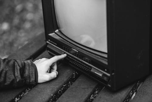 Black and white of unrecognizable male pressing buttons on old fashioned television placed on wooden table in nature on blurred background