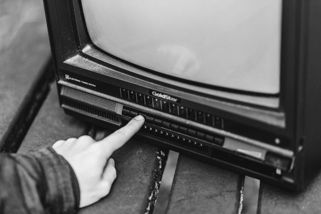 Black and white from above of anonymous male switching channels on retro black television placed in wooden table on street