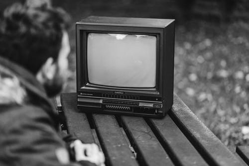 Black and white side view of anonymous male sitting at wooden table and looking at old fashioned television in nature on blurred background