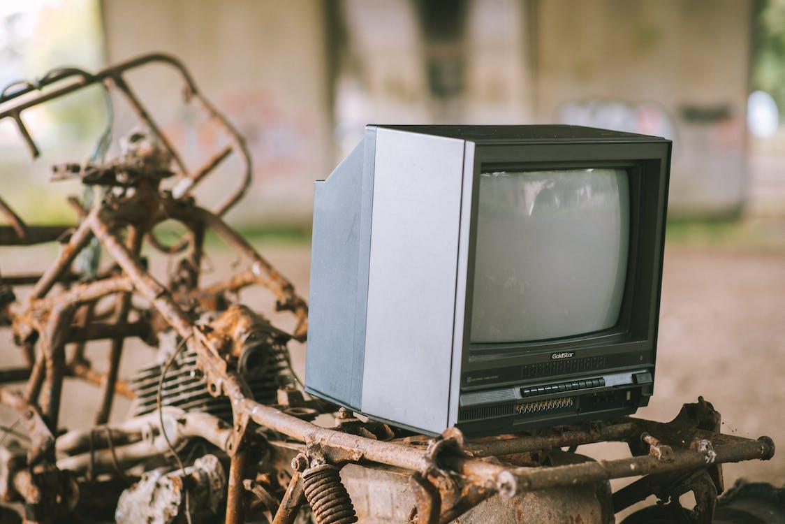 茶色の木製テーブルの上の黒いブラウン管テレビ