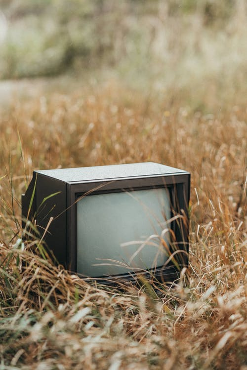Small black abandoned old fashioned television placed on dried faded grass in countryside with trees on blurred background in nature
