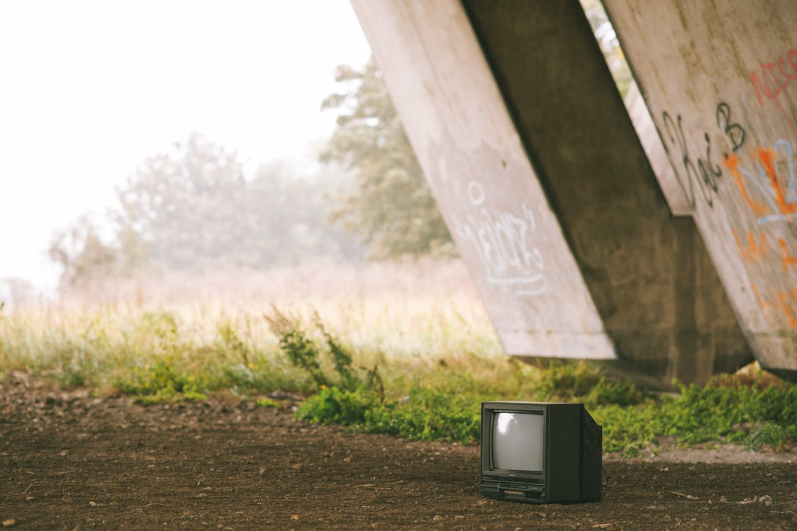 Small black old fashioned television placed on ground near concrete construction with graffiti and grassy terrain with trees on foggy background