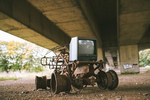 Old damaged vehicle with vintage television set on rough pathway under bridge in sunlight