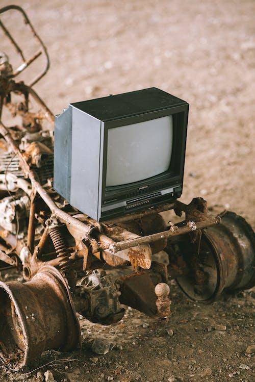 Vintage television set on rusty vehicle on pathway