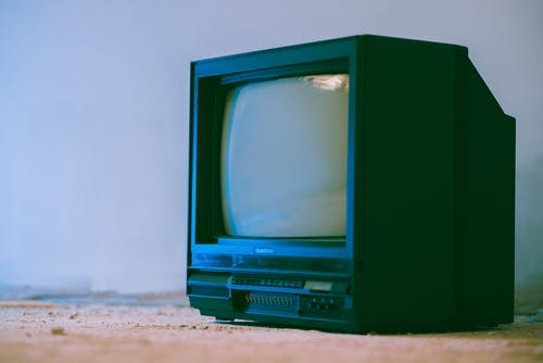 Aged television set with control panel and plastic case near wall in building on white background