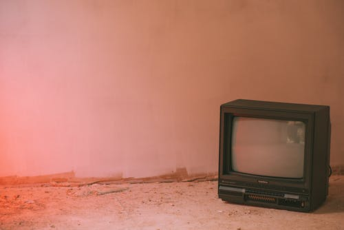 Aged television set reflecting old house near wall