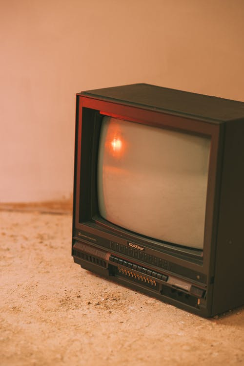 Old fashioned television set with cathode ray tube display on rough floor in house
