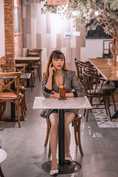 Young pondering ethnic female in elegant apparel touching face at table with refreshing drink while looking away in cafe