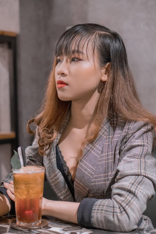 Young wistful Asian lady with makeup in stylish clothes looking away at table with refreshing drink in cafeteria