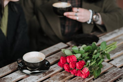 Crop anonymous man with cup of cappuccino interacting with girlfriend at wooden table with blooming flower bouquet