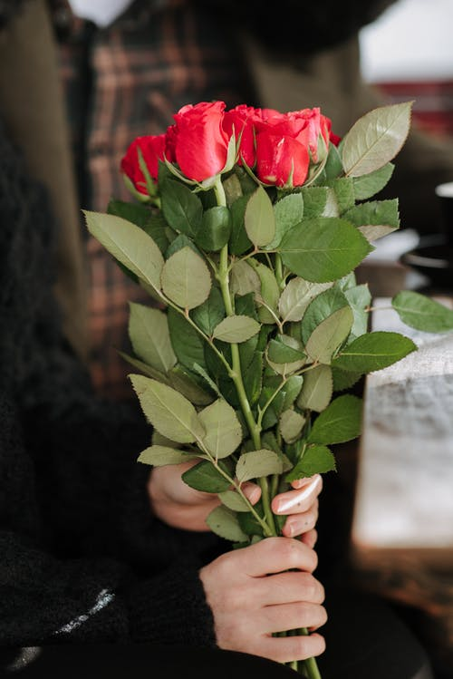 Crop anonymous female with blossoming red flowers at table near male beloved in cafeteria
