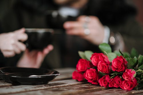 Crop unrecognizable couple with cups of beverages at wooden table with blossoming flowers in cafeteria