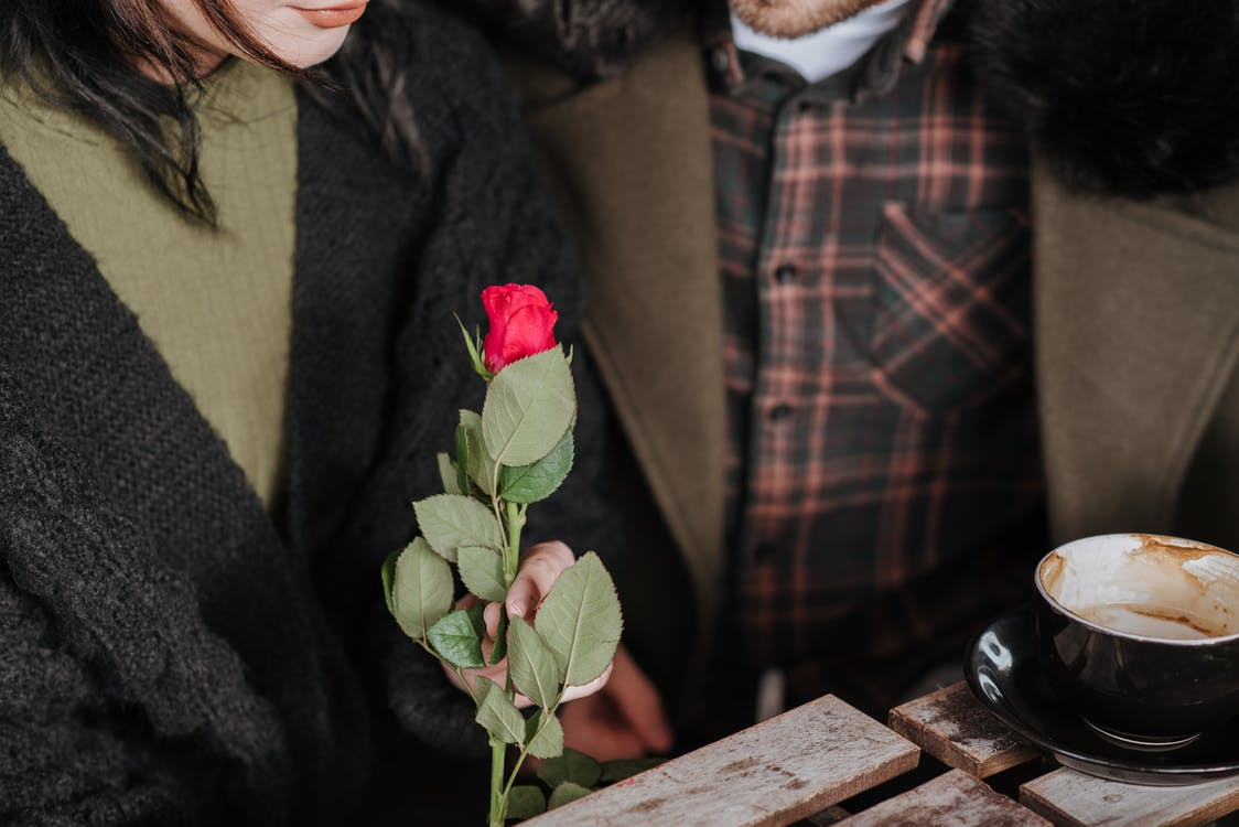 Unrecognizable couple with rose and cappuccino in cafe
