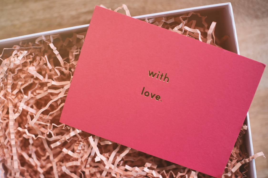 From above of rectangular shaped greeting card representing With Love inscription on cardboard box with organic shavings