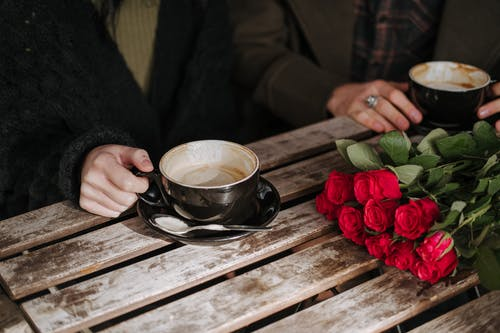Faceless couple with cappuccino and blooming flowers in cafe