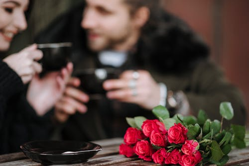 Crop couple with coffee interacting at cafe table with flowers
