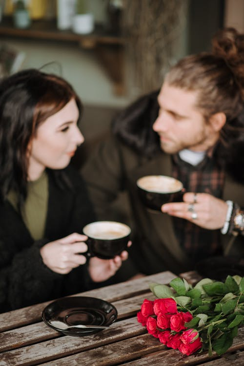 Crop young smiling woman talking to boyfriend with cup of cappuccino while looking at each other at cafeteria table with blossoming roses