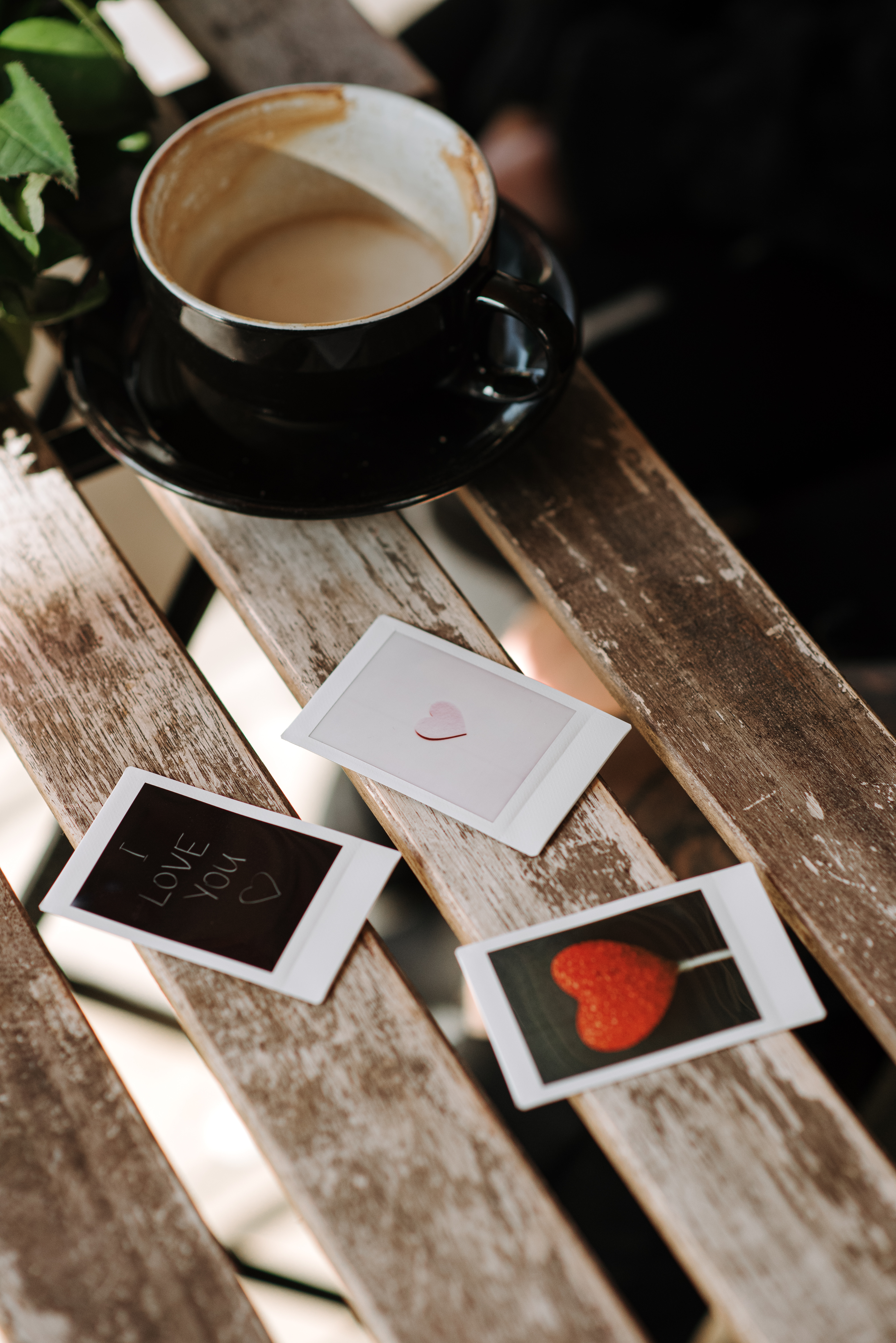 assorted instant photos with heart symbols near cup of cappuccino