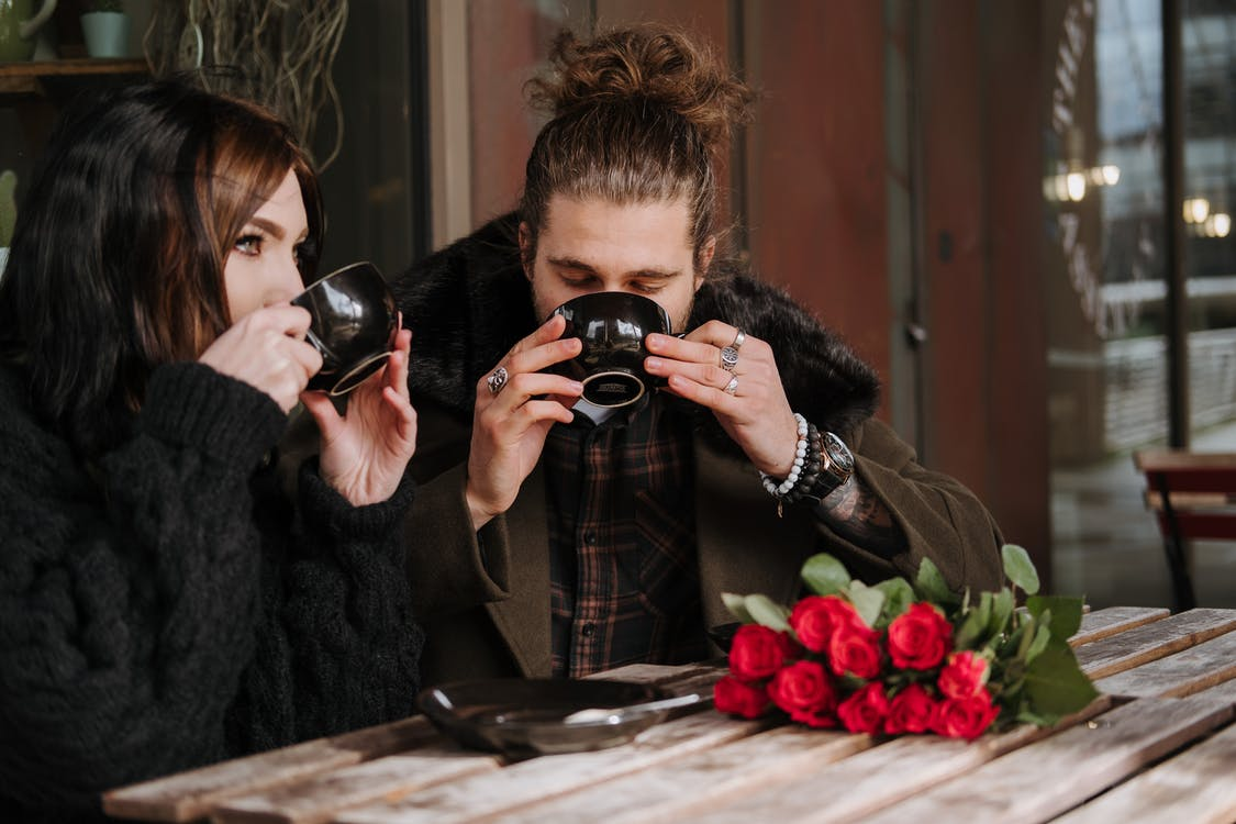 Couple enjoying delicious coffee at cafe table with blossoming roses