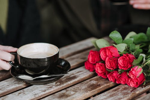 Crop unrecognizable couple with cup of delicious cappuccino at wooden table with blooming red flowers