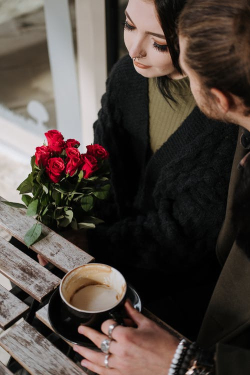 From above of crop anonymous man with cup of cappuccino talking to charming female beloved with flowers in cafeteria