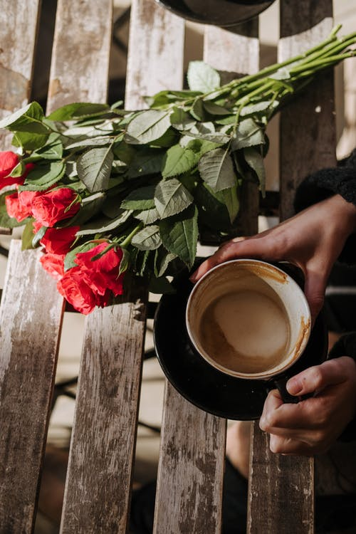 Crop person with cup of cappuccino and roses in cafe